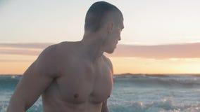 Sluit omhoog van knappe mscular mens status op zee vermoeid na zwemmen stock footage