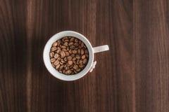 Sluit omhoog van koffiebonen in een kop Stock Fotografie