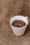 Sluit omhoog van koffiebonen in een kop Stock Foto's