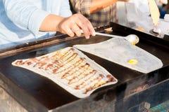 Sluit omhoog van kok bradende pannekoeken bij straatmarkt Royalty-vrije Stock Foto