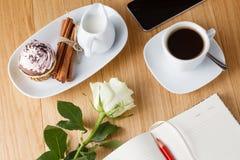 Sluit omhoog van kop van koffie en notitieboekje op een houten lijst Royalty-vrije Stock Fotografie
