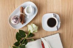 Sluit omhoog van kop van koffie en notitieboekje op een houten lijst Royalty-vrije Stock Foto