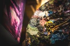 Sluit omhoog van kunstenaarsborstels en olieverven op houten palet stock afbeeldingen