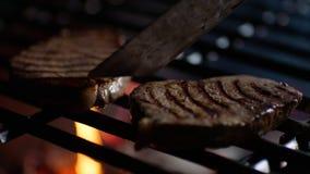 Sluit omhoog van lapjes vlees bij de restaurantgrill met brandvlammen, draait de chef-kok hen over, langzame motie stock footage