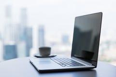 Sluit omhoog van laptop en koffiekop op bureaulijst stock foto's