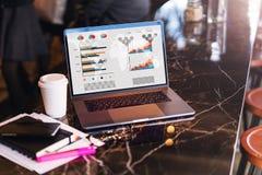 Sluit omhoog van laptop met grafieken, grafieken op het scherm, notitieboekje, kop van koffie op lijst in lege koffie zonder mens stock fotografie