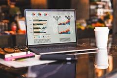 Sluit omhoog van laptop met grafieken, grafieken op het scherm, notitieboekje, kop van koffie op lijst in lege koffie zonder mens stock afbeelding