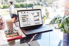 Sluit omhoog van laptop met grafieken, grafieken op het scherm, notitieboekje, kop van koffie op lijst in lege koffie zonder mens royalty-vrije stock fotografie