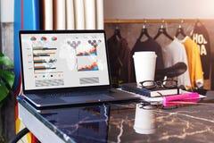 Sluit omhoog van laptop met grafieken, grafieken, programma op het scherm, notitieboekje en kop van koffie op lijst in lege koffi royalty-vrije stock afbeelding