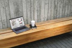 Sluit omhoog van laptop met grafieken, grafieken, programma's op het scherm en kop van koffie op benchoutdoor Computer op houten  royalty-vrije stock foto