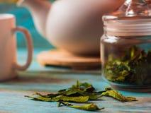 Sluit omhoog van los blad groene thee op rustieke achtergrond Witte theepot en koppen met groene thee op een achtergrond Stock Afbeeldingen