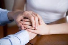 Sluit omhoog van man en vrouwenholdingshanden die steun tonen stock fotografie
