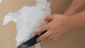 Sluit omhoog van man hand die een verf op een oude huismuur pellen stock video
