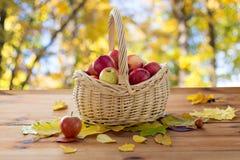 Sluit omhoog van mand met appelen op houten lijst Stock Afbeeldingen