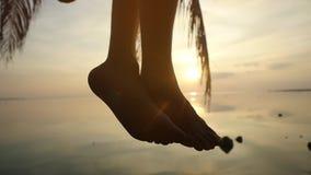 Sluit omhoog van mannelijke benen De jonge mens zit op een palm golvende benen bij tropisch strand tijdens mooie zonsondergang La stock footage
