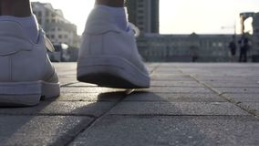 Sluit omhoog van mannelijke benen die zich in witte tennisschoenen, de reclame van het sportschoeisel bewegen stock video