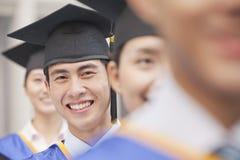 Sluit omhoog van Mannelijke Gediplomeerde Student Standing op een rij van Gediplomeerden Stock Fotografie