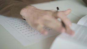 Sluit omhoog van mannelijke hand invullend een spatie met meerkeuzequiz stock footage