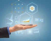 Sluit omhoog van mannelijke hand met smartphone en hologram Stock Foto's