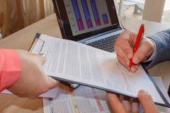 Sluit omhoog van mannelijke hand zettend handtekening in het contract, schriftelijke verklaring verklarend de prijs bedrijfsvenno Royalty-vrije Stock Afbeeldingen