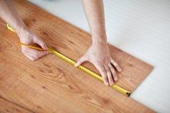 Sluit omhoog van mannelijke handen die bevloering meten Stock Fotografie