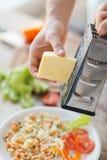 Sluit omhoog van mannelijke handen die kaas over deegwaren raspen Stock Foto's