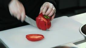 Sluit omhoog van mannelijke handen snijdend verse rode groene paprika met mes stock footage