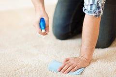 Sluit omhoog van mannelijke schoonmakende vlek op tapijt stock afbeelding