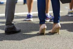 Sluit omhoog van mannen en vrouwenbenen in verschillende schoenen, hoge hielen wa Royalty-vrije Stock Fotografie