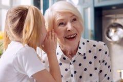 Sluit omhoog van meisje die haar grootmoeder een geheim vertellen stock afbeelding