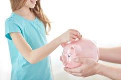 Sluit omhoog van meisje die muntstuk zetten in spaarvarken Royalty-vrije Stock Foto's