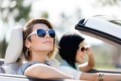 Sluit omhoog van meisjes in zonnebril in de witte auto Stock Foto's