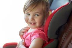 Sluit omhoog van meisjezitting in miniatuurautozetel stock afbeelding