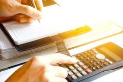 Sluit omhoog van mens die met calculator die nota's de maken thuis, h tellen Royalty-vrije Stock Foto's