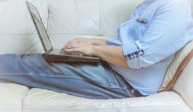 Sluit omhoog van mens die met laptop computer werken en op bank de zitten Stock Fotografie