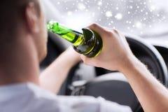 Sluit omhoog van mens het drinken alcohol terwijl het drijven van auto Stock Afbeeldingen
