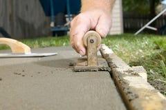Sluit omhoog van mens het eindigen cement met het scherpen van hulpmiddel Royalty-vrije Stock Foto