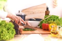 Sluit omhoog van menselijke handen die plantaardige salade in keuken op de glaslijst koken met bezinning Gezonde maaltijd, en stock foto's