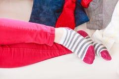 Sluit omhoog van menselijke vrouwenvoeten in gestreepte sokken stock fotografie