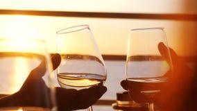 Sluit omhoog van mensen die glas wijn houden, makend een toost over zonsondergang Vrienden die witte wijn drinken stock foto