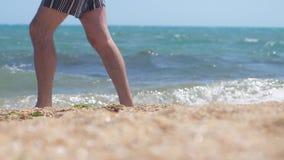 Sluit omhoog van mensen` s voeten lopend langs het zandige strand van het overzees, langzame motie 1920x1080 stock video