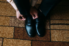 Sluit omhoog van mensenbeen en handen die modieus zwart schoenkant binden die zich op tapijt met rechthoekig ornament bevinden Stock Afbeelding