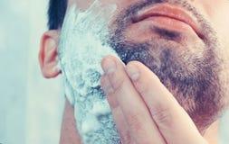 Sluit omhoog van mensengezicht die een schuim op zijn kin op een lichte rug toepassen Royalty-vrije Stock Fotografie