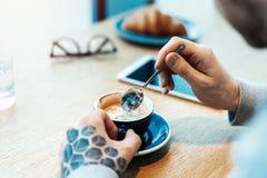 Sluit omhoog van mensenhanden houdend kop van koffie Het croissant is op achtergrond stock foto