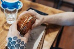 Sluit omhoog van mensenhanden met tatoegering houdend verse sappige hamburger bij koffie royalty-vrije stock foto's