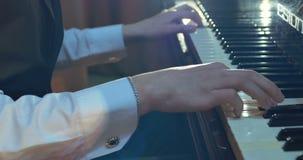 Sluit omhoog van mensenhanden spelend op piano stock footage