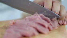 Sluit omhoog van mes het snijden door vlees stock video