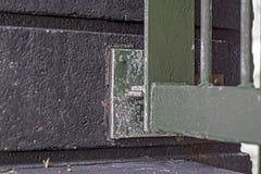 Sluit omhoog van metaalbarrière aan een concrete muur wordt aangesloten bij die stock fotografie