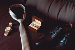 Sluit omhoog van moderne bruidegomtoebehoren trouwringen in een bruine houten doos, een stropdas, leerschoenen en horloge Stock Foto's