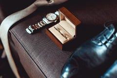 Sluit omhoog van moderne bruidegomtoebehoren trouwringen in een bruine houten doos, een stropdas, leerschoenen en horloge Royalty-vrije Stock Afbeelding